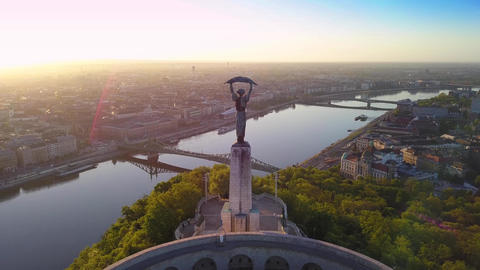 Aerial footage of flying around Statue of Liberty with Budapest sunrise skyline Footage