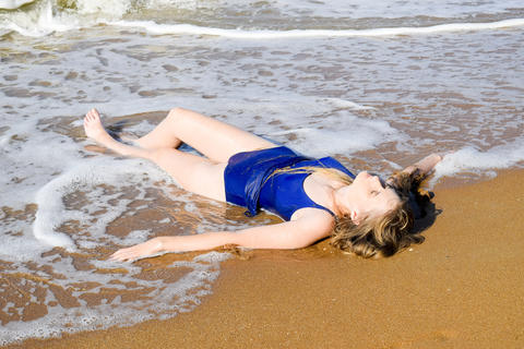 Girl in a blue bathing suit lies on the seashore and relaxes. Waves caress the Photo