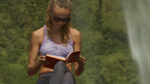 Lady in Violet Top Reads Diary Book on Large Rock Footage