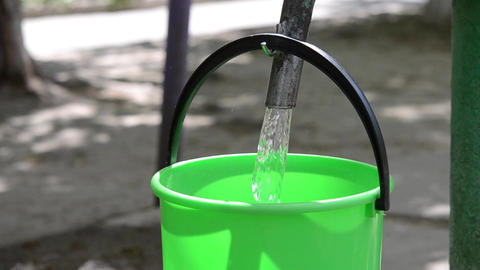 A man pours water in a plastic bucket 영상물
