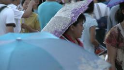 People in rain walk on street city of Tiananmen Square Footage