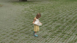 Child walking on streets of city in park Footage
