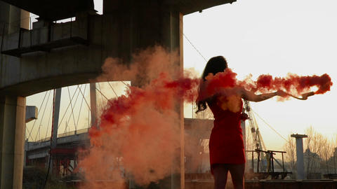 Beautiful stylish woman in red dress dance with red smoke in slowmotion Live Action