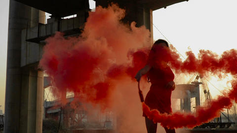 Young woman in red dress dancing with red smoke near abandoned bridge Footage