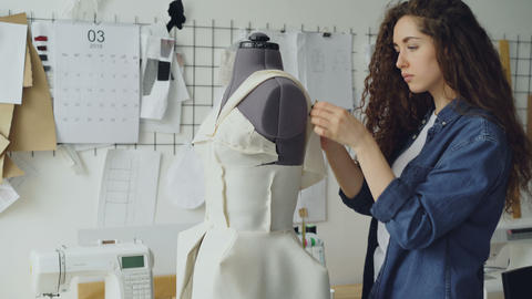 Young female tailor is adjusting clothes on tailoring dummy with sewing pins and Footage
