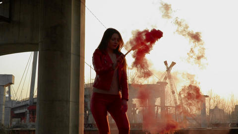 Elegant girl in red costume dancing with red smoke near old constructions Footage