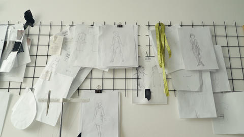 Clothing design sketches, black and white templates and drawings pinned on white Footage