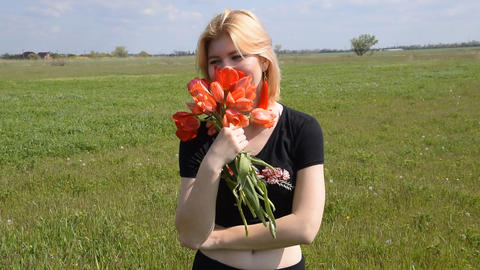 The blonde smells a bouquet of tulips. Girl with a... Stock Video Footage