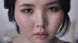 Portrait of young asian brunette girl, looking at camera, serious face, sad eyes Footage
