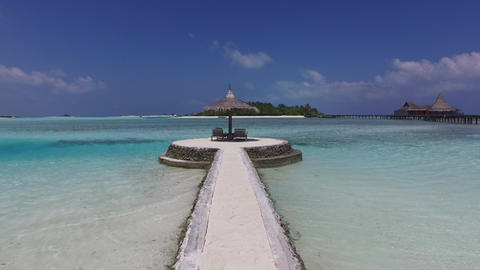 palapa and sunbeds on maldives beach pier over sea Footage