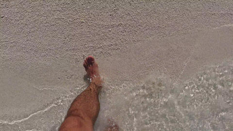 male feet walking out sea water to beach sand Footage