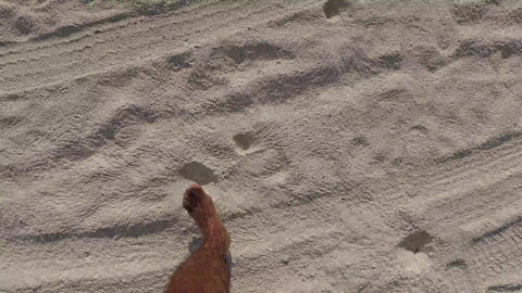 male feet walking along sandy beach Footage