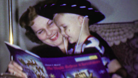 1957: Mother cowboy hat toddler boy read Christmas bedtime book Footage