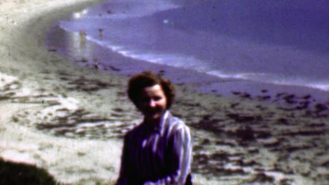 1958: Women resting beachside enjoying light ocean wave action Footage