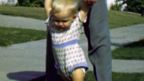 1958: Dad helps baby boy learn walk front yard suburban sidewalk Footage