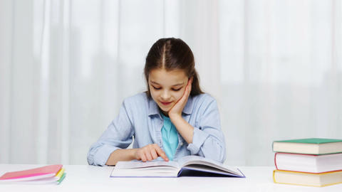 happy school girl reading book or textbook at home Footage