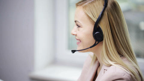 businesswoman with computer and headset talking Footage
