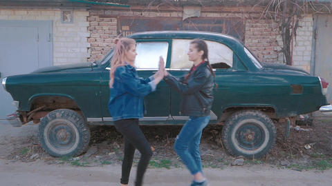 Two beautiful young women giving high five - Pretty girls on a old retro car Footage