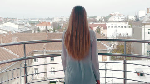 A young woman goes to the railing balcony and admires the city's landscape Footage