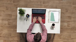 Top View of an office worker sitting at his desk, typing on red laptop, coffee Footage