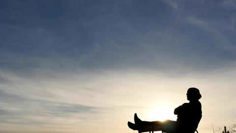 Laying relaxed man silhouette on sky background time lapse Live Action