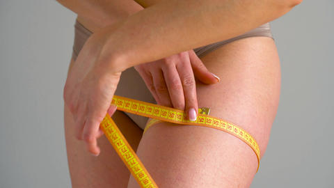 Woman measures her leg with measuring tape Footage