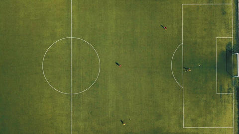 Aerial view of football team practicing at day on soccer field in top view Footage