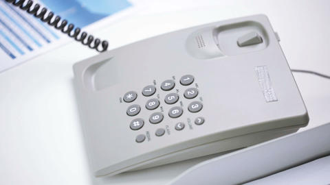 hands dialing number on desk set phone at office Footage
