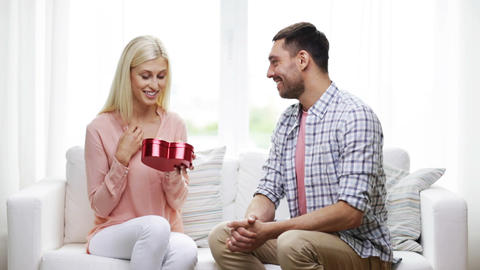 man giving woman red heart shaped gift box Footage