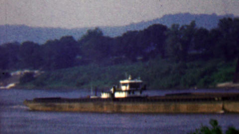 1957: Barge flatbed transport ship heading upriver in rural setting Footage