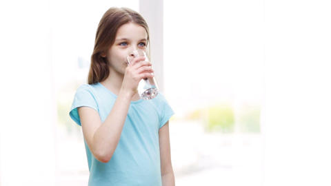 happy smiling little girl drinking water at home Footage