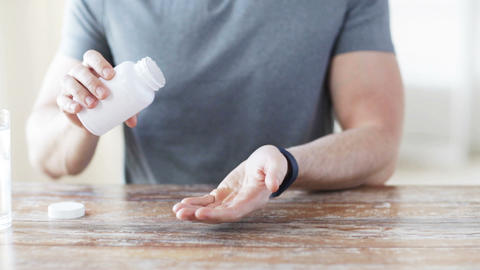 Close Up Of Man Pouring Pills From Jar To Hand stock footage