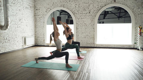 Female yoga class is practicing warrior position then moving into plank pose Footage