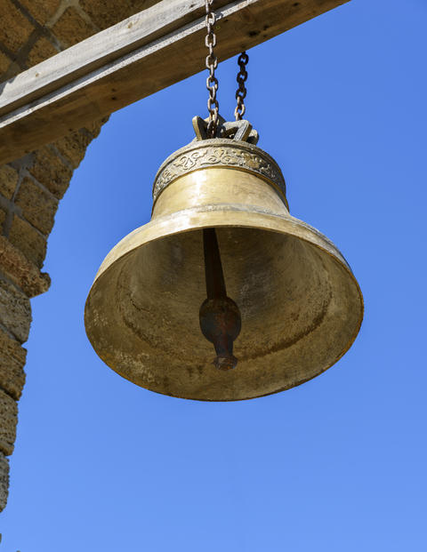 a large copper bell hanging on a wooden crossbeam フォト