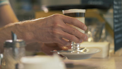 Barista putting prepared coffee latte in glass cup on table in cafe close up Footage