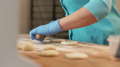 Baker hand rolling dough before baking pastries on table in bakehouse close up Footage