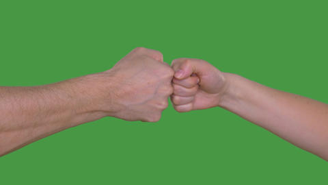 One fist beating another fist isolated on green background. Alpha channel, keyed Footage