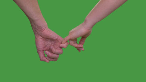 Male hand holding female hand on little finger on green background close up Footage
