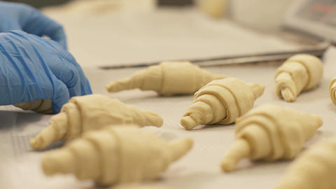 Close up croissant lying on paper in tray before baking in confectionary shop Footage