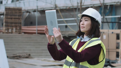Construction worker taking picture with digital tablet of project development Footage