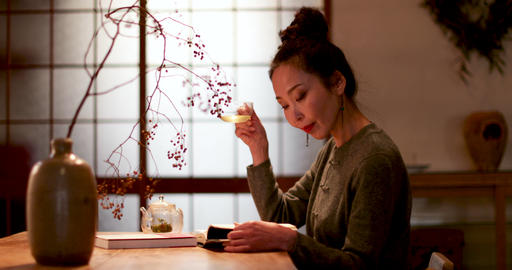 Japanese female reading book at home and drinking tea, Kyoto Japan Footage
