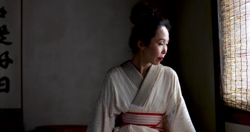 Japanese woman wearing Kimono by traditional window, Kyoto Japan GIF