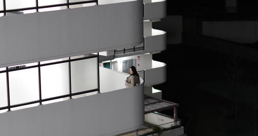 Woman standing on balcony at night. Tokyo, Japan Footage