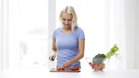 smiling young woman chopping tomatoes at home Footage