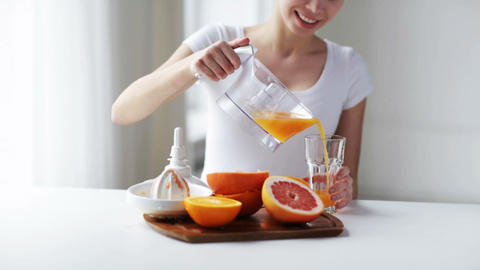 woman with squeezer pouring orange juice to glass Footage