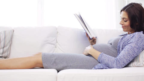 happy pregnant woman reading book at home Footage