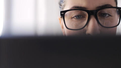 young woman in eyeglasses with laptop at home Footage