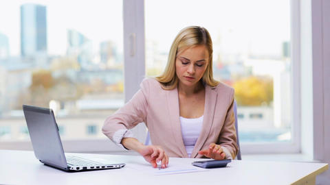 businesswoman with laptop, calculator and papers Live Action