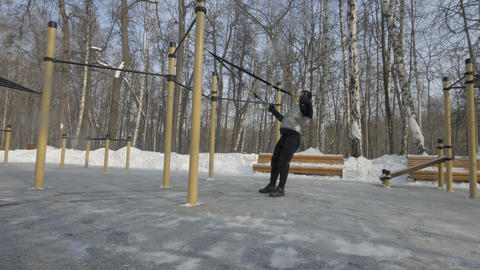 Young man training with fitness straps on winter sport ground outdoor Footage