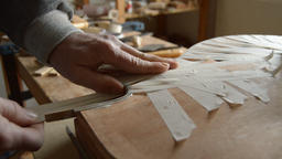 Luthier sticking the wooden edges with paper tape of a jazz electric guitar 영상물